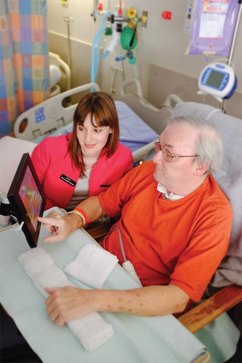 Bob Henry works with LHSC Speech Language Pathologist on a specially fitted iPad that is now available to patients in the ICU