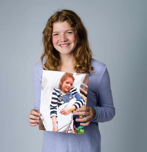 A happy and healthy Teaghan holds a photos of her younger self during an enzyme replacement therapy drug infusion at Children's Hospital at LHSC